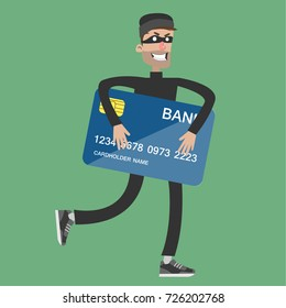 Stealing bank card. Thief in black outfit and mask holding credit card.