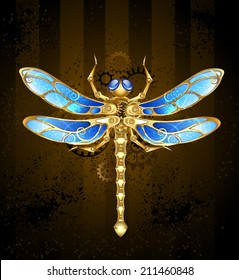 Steampunk mechanical dragonfly brass and gold with wings decorated with blue glass and gears.