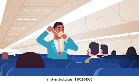 steward explaining for passengers how to use oxygen mask in emergency situation african american male flight attendant safety demonstration concept modern airplane board interior horizontal vector