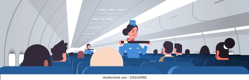 stewardess explaining passengers how to use seat belt fastening in emergency situation flight attendants in uniform safety demonstration concept airplane board interior horizontal vector illustration