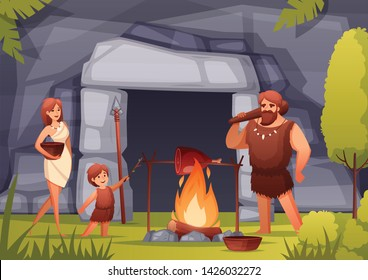 Stone age prehistoric family cooking meat over open fire in front of cave entrance flat composition vector illustration