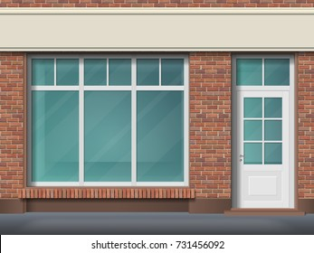 Store front with large transparent window. Facade of red brick. Empty glass showcase of boutique. Entrance in the small  shop.