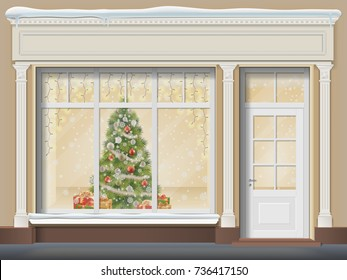The storefront  with a door and a large window. Christmas showcase decorated with a xmas tree, glowing garland, snowflakes and gift boxes.