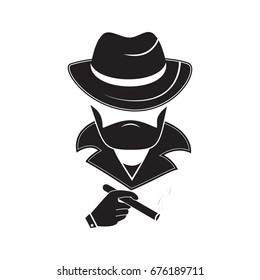 A stranger in a hat holds a smoking cigarette in his hand. Mafia style