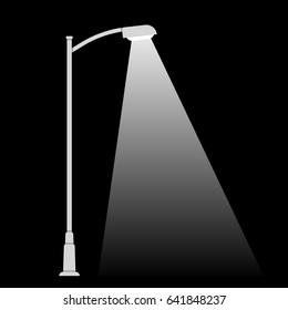 Streetlight lamp post on dark background with spotlight beam. Simple black and white vector illustration.
