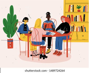 Students sitting together at table with books and studying