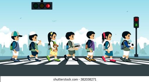 Students walk across the crosswalk with a traffic light.