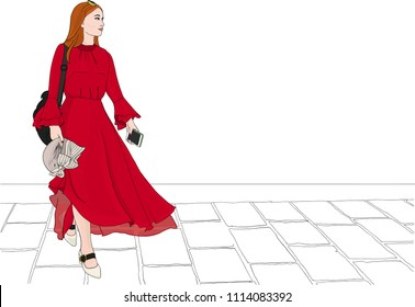 Stylish, fashionable woman in a flowing red dress with transparent chiffon walks over a cobblestone street  in a European city.