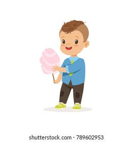 Stylish preschool kid standing with sweet cotton candy. Cartoon little boy character with brown hair in blue shirt and brown pants. Flat vector design
