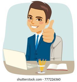 Successful happy businessman making thumbs up gesture sitting on office desk with laptop