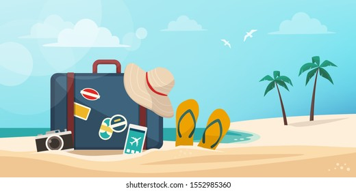Suitcase, camera, smartphone and beach accessories on the sand: vacations on the tropical beach concept