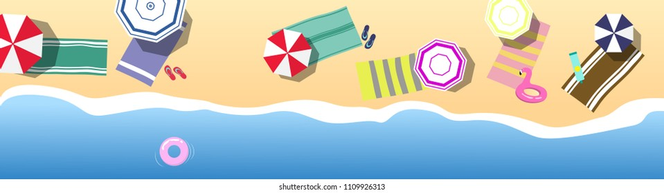 Summer holidays concept. Top view on beach with sea / ocean and pink life ring, colorful umbrellas and towels, pink inflatable flamingo flip-flops and cream for sunbathing on the sand.