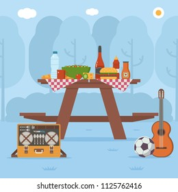 Summer wooden picnic table on forest background. Family barbecue concept with picnic party stuff. Guitar, straw basket, wine and food for outing on public park.