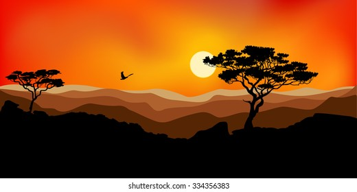 Sunset in the mountains lonely trees and the flying bird