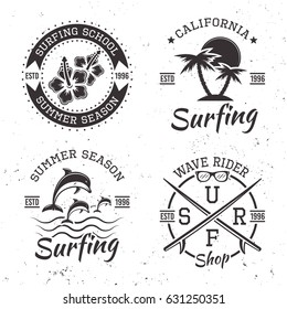 Surfing set of four black vector emblems, badges, labels and logos in vintage style isolated on white background with grunge texture
