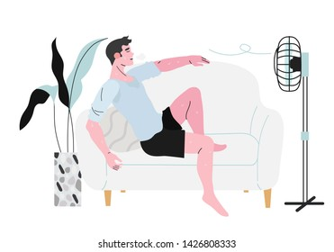 A sweaty man sitting on a sofa in front of a fan during hot summer days and not feeling well because of the terrible heat.