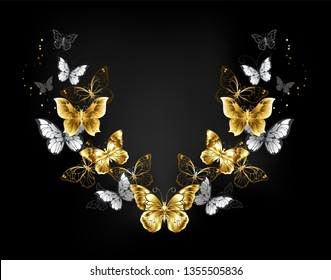 Symmetrical pattern of gold, jewelry and white butterflies on black background. Golden butterfly.