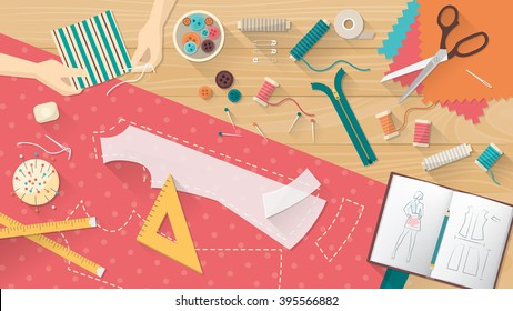 Tailor working and sewing a shirt, sewing equipment, patterns and sketchbook on the work table, dressmaking concept