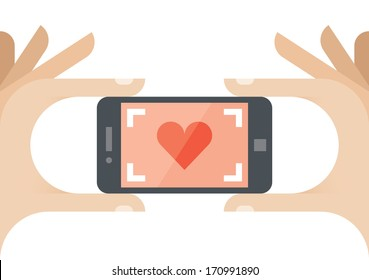 Taking a photo of Love with red heart on the screen of mobile phone