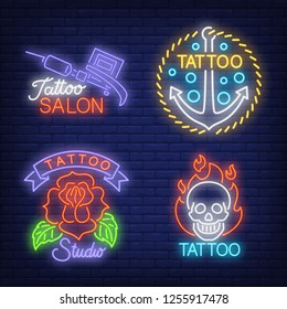 Tattoo machine, anchor, rose and skull neon signs set with text. Tattoo salon advertisement design. Night bright neon sign, colorful billboard, light banner. Vector illustration in neon style.