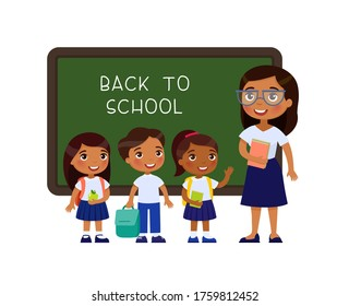 Teacher greeting pupils in classroom flat vector illustration. Boys and girls dressed in school uniform and female teacher pointing at blackboard cartoon characters. Primary students back to school