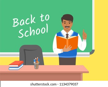Teacher Indian man standing with open book at the blackboard in classroom. School class interior. Traditional education concept. Vector cartoon illustration. Back to school banner.