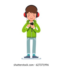 Teen boy in big headphones listening to music on mobile phone. Young man wearing hoodie, jeans and kids standing and tapping smartphone. Flat style character vector illustration isolated on white.