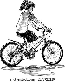 A teen girl rides a bicycle