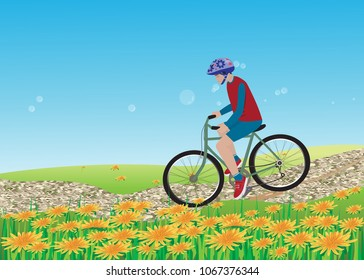 A teenage boy with a helmet ride a bicycle through the dandelion field