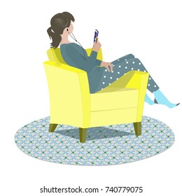 Teenage girl dressed in pajama listening to music on her phone seated on a armchair