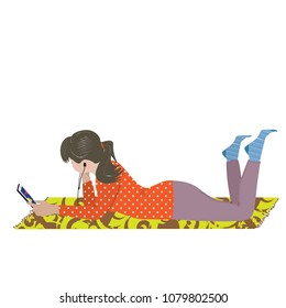 The teenage girl lying relaxed on the rug and listening to music on the mobile phone
