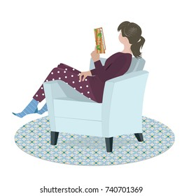 The teenage girl in pajama sits relaxed in her armchair and reads the book