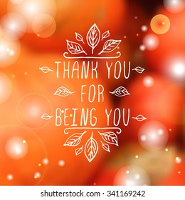 Thank you for being you. Hand sketched graphic vector element with leaves and text on blurred background. Thanksgiving design.