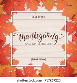Thanksgiving Day sale banner. Hand lettering on the wooden background with trendy autumn foliage.
