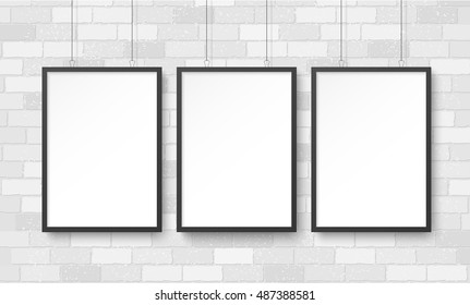 Three blank poster mockup on white brick wall