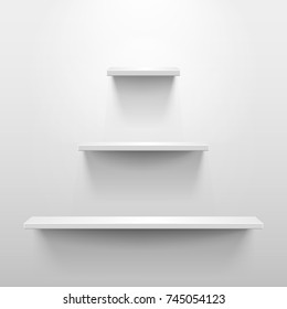 Three shelves on the wall with light and shadow in empty white room. Pyramid or tree shape