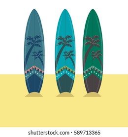 Three surfboards on the sand.