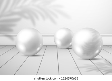 Three white shiny balls on a plank floor. A shadow of palm tree leaves on a white wall behind