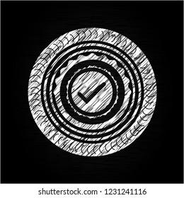 tick icon inside chalkboard emblem on black board