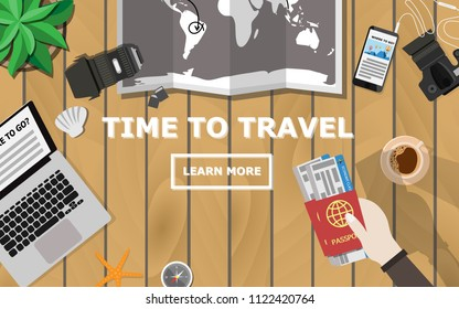 """Top down flat lay view of wooden table with laptop, camera,lens,mobile phone,coffee,hand holding passport and plane ticket,world map,compass,tree and copy space for text""""Time to Travel"""""""