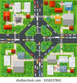 Top view of the colorful city with a road highway traffic jams motorway with roofs of houses, cars, streets and trees