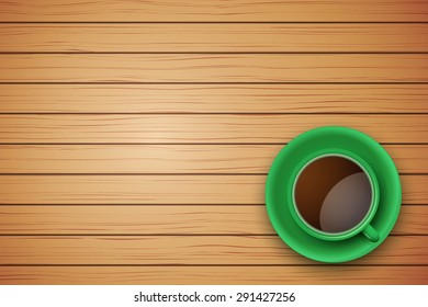 Top view of green cup of coffee or tea on the table light wood with space for text
