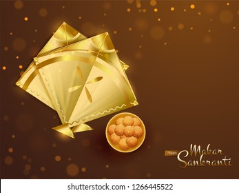 Top view of shiny golden kites and indian dessert on brown bokeh background for Happy Makar Sankranti festival celebration.
