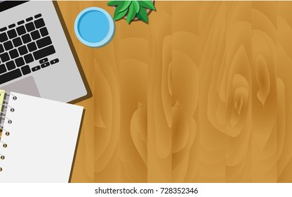 Top view of wooden working desk with laptop, a glass of water, and empty paper note with copy space for your own text
