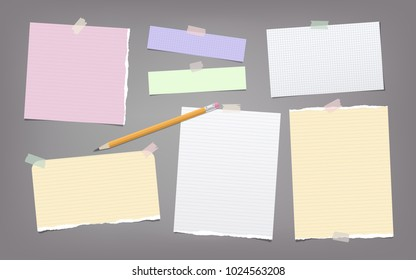 Torn colorful and white note, notebook paper strips, sheets, pencil for text stuck with adhesive tape on dark gray background.