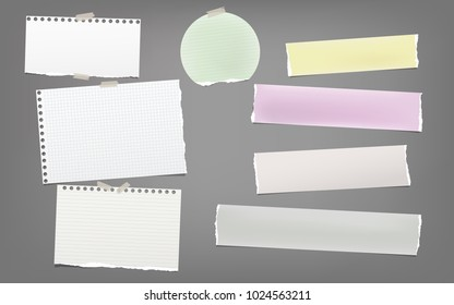 Torn colorful and white note, notebook paper strips, sheets for text stuck with adhesive tape on dark gray background.