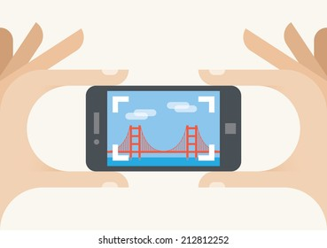 Tourist mobile phone camera taking Golden Gate bridge photo, San Francisco, California. Concepts: photography sharing services (Instagram), tourism, holiday, travel, famous places, vacation, blogging