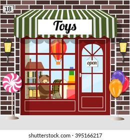 Toy shop (toy store) building facade. Brown brick. Doll house, bear, balloon and drum in the window. EPS 10 vector.