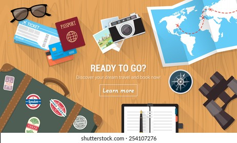 Traveler's desktop with suitcase, camera, plane ticket, passport, compass and binoculars, travel and vacations concept