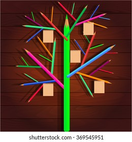 Tree of crayons, paper on the branches, on wood texture